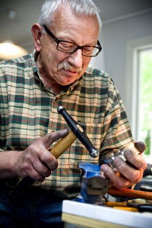 Olle Sundin bearbetar en liten silverskål, vid sitt lilla verkstadsbord.