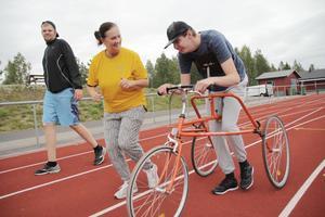 Carina Karlsson, ledamot i Svenska Downföreningen, peppar igång Kristoffer Westrin som provar en springcykel för allra första gången. Till vänster försökte Henrik Spjut hålla jämna steg.