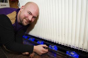 Jonny Widell vid ett av elementen i sitt hem, där han har placerat sju datorfläktar.