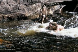 Här tar sig Emil Forsblom ner i vattnet. Det gäller att vara försiktig så man inte halkar på de våta klipporna. Bäst är faktiskt att sitta ner både på land och i vattnet när man ska framåt.