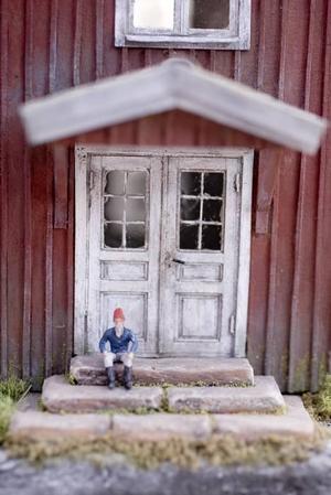 FÖRSTUKVISTEN TILL NÄRKESTUGAN. Dörren bakom gårdstomten är detaljerad med gångjärn, dörrtrycke och lackad plast som fönsterglas för det handblåsta utseendet.