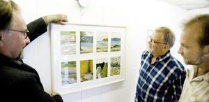 Göran Strandow hänger upp sina konstverk i den lilla utställningslokalen på Öster.