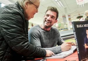 Linus Larsson signerar en julklapp åt Ann-Marie Karlström-Tora på ICA Nyplan i Sandarne.