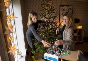 Asken med gammalt julpynt hittade Maria och Anna i ett rivningshus. Tapeten kommer från Boråstapeters kollektion Karlslund, inspirerad av 1880-talet. Skåpet är nytt från Ikea.