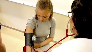 Lärarinnan Siska Laurila tar blodtrycket på eleven Fanny Brandberg.