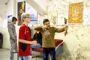 Abdallah M. Alaamar, 11 år, testar på bågskytte och får hjälp av klubbens Herman Westling, 12 år.