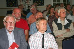 30 personer kom till vindkraftskvällen på Bergsjögården. De två andra medverkande, Bengt Andreasson. t.v och Torkel Berg, lyssnar när Anders Bergströms gör sin dragning