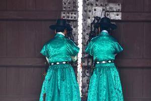 Traditionella vakter väntar på att få slå upp porten.