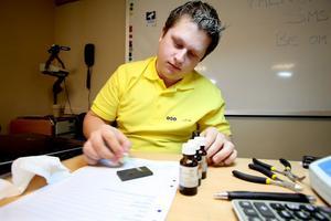 Med en probersten och kungsvatten fastställer Jan Fredlund hur många karat guldföremålen har.