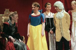 Snövit i gul kjol tillsammans med prinsen och den elaka styvmodern i guldtronen.
