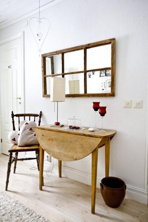 I hallen har Lena gjort ett arrangemang som innehåller små detaljer med rött - en favoritfärg. Bordet kommer från sommarstugan Lena och hennes man köpte innan de ens flyttat ihop.