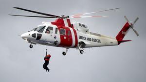 En räddningshelikopter av typen Sikorsky S-76 vinschar under övningen  SkagEx 11 i Oslofjorden nordväst om Strömstad.