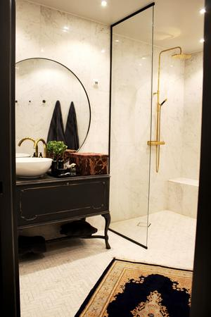 Badrum i vit marmor och detaljer i guld.