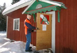 Lars G Engström visar runt vid Alfta Skogskarlars anläggning på Stafsberg, På dörren till stugan sitter föreningens emblem.
