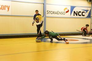 Christoffer Sundgren coachar en ungdom som ville prova på curling.