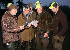Harebragängets Rune Jönsson och Rolf Pellving längst till vänster kollar kartor inför dagens jakt.