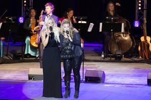 Samsjungna kompisar, Malena Ernman och Sarah Dawn Finer, med Magnus Lindgren på saxofon i bakgrunden.