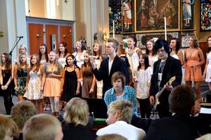 Skolkören ackompanjeras av en grupp musiker under avslutningsprogrammet i Nora kyrka.