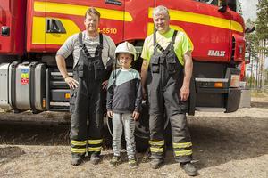 Brandmännen Mikael Gårdman till vänster, och Bo Eriksson till höger, tillsammans med Simon Lindh från Mora som fick prova en hjälm.