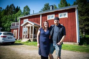 Elin och Andreas framför sitt röda hus med vita knutar.