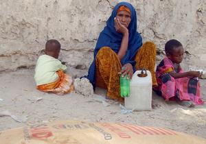 En somalisk kvinna och hennes barn väntar på att få mat via en organisation. Foto: Farah Abdi Warsameh, AP Photo