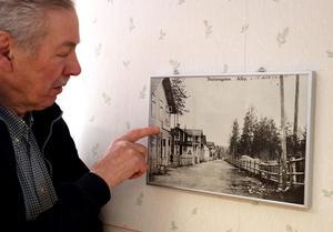 Carl Erik Decker visar bilden som hänger på en vägg i närcentralen, och som visar hur det såg ut i Alby under samhällets forna glansdagar.