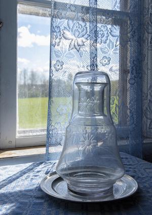 En glasflaska på ett bord framför en skir spetsgardin. Foto: Ulrika B Höglund