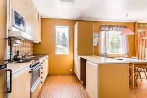 Köket går i orange och brunt. Foto: Länsförsäkringar Fastighetsförmedling