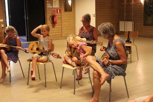 Barn och vuxna lär sig spela folkmusik på gitarr.