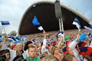 Ester viftar med estniska flaggor under en sång och dansfestival i Tallinn.