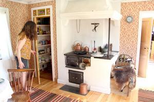 Nytt skafferi av gammal dörr och litet fönster ovanför.