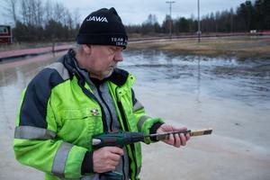 Rolf Åström mäter tjockleken på isen med en borr och tumstock.