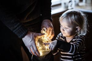 Aili Persson studerar en julkula med belysning.