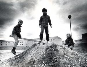 Bjurhovda 30 september 1970. Bildtexten i vlt löd så här: När ingen annan gör något för att vi ska få någonstans att leka, så får vi väl göra det själva, tycks barnen i Bjurhovda resonera. På bilden gungar Bosse Sandberg och Urban och Mikael Vallin på det provisoriska gungbrädet.