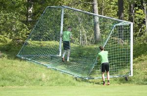 Anton Liljenbäck och Max Watson fick äran att skjuta ena målet åt sidan för att göra planen redo för gräsklippning.