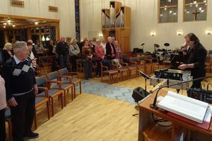 """Publiken har rest sig upp vid """"Sjung med oss i sången"""". Sjunger med gör Bo Westberg Gren, som utformat den färgrika altartavlan med fönsterglas från Lillkyrkan. Foto: Kjell Larsson"""