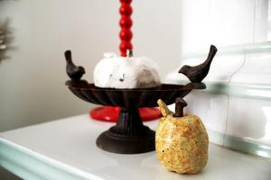 Ett fågelbad i gjutjärn står tillsammans med två äpplen skapade av Lotta.