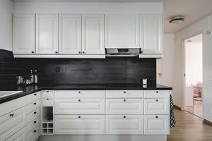 Kök i vitt och svart med öppen planlösning mot vardagsrummet. Foto: Ralph Welin