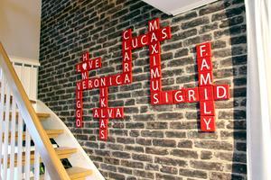 Röda alfapetbrickor som bildar familjemedlemmarnas namn är sammanlänkade som korsord.