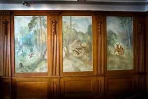 Den fantastiskt vackra väggpanelen har mönster som är utskuret direkt i träet. Jaktmotiven mellan panelen målades under renoveringen 1916.