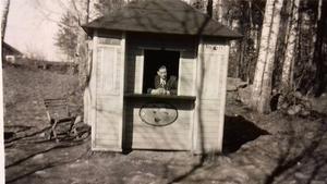 """Harry Gidlund i kiosken vid Mellandammen, delad på Facebook av Roger Johansson. """"Antar att den måste ha levt på dem som skulle dansa i Folkets park eller möjligen på dem som gick en promenad i området"""", spekuleras det på Facebook. Stenmuren till höger om kiosken ska finnas kvar än idag liksom uthuset som syns i bakgrunden. Foto: Privat"""