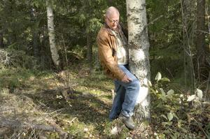 Sven-Erik Persson visar hur hans hustru Karin fick benet i kläm mot trädet.