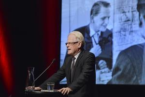 Ingvar Carlsson (S), före detta statsminister. framför en bild av Olof Palme.