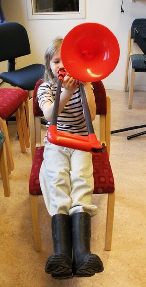 Flickan med den röda trombonen heter Linn Karlsson. Hon är 7 år och kommer från Trönö.