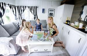 I sommarstugan finns ett litet men funktionellt vardagsrum där familjen kan spela spel på kvällarna.
