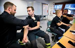 Här övar, från vänster, Nicklas Backman, Anton Eriksson, Emelie Lahti och Jairo Hincapie med att använda en tourniquet. Det gör ordentligt ont i armen när blodflödet stoppas helt.