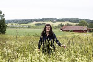 Karin på väg upp till skogen ovanför gården. Nedanför gården ligger sjön Åsgarn.