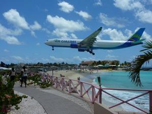 Ligga och bada i kristallklart karibiskt vatten vid en strand under stora jumbojetsens inflygningar mindre än 50 m från landningsbanan.