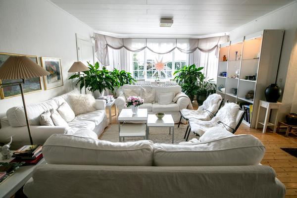 Vardagsrummet är stort och har utsikt mot trädgården och en vattenspegel.