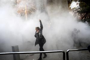 En student vid en protest vid Teherans universitet, där polisen satte in rökgranater mot demonstranterna.Foto: AP/TT
